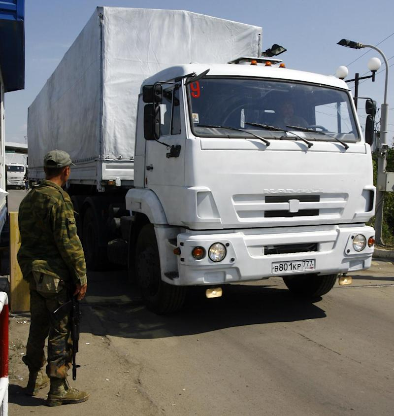 A pro-Russian militant stands next to the lift gate as lorries, part of a Russian humanitarian convoy cross the Ukrainian border at the Izvarino custom control checkpoint, on August 22, 2014
