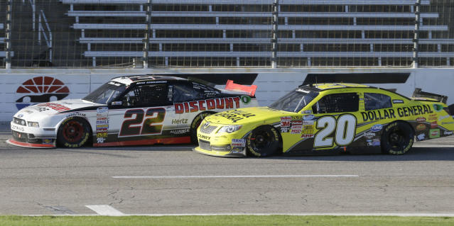 Brad Keselowski (22) pulls away from Denny Hamlin (20) during the NASCAR Nationwide Series auto race at Texas Motor Speedway in Fort Worth, Texas, Saturday, Nov. 2, 2013. Keselowski went on the win the race. (AP Photo/Larry Papke)
