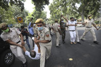 Policemen carry away members of India's opposition Congress party during a protest against agriculture bills in New Delhi, India, Monday, Sept. 21, 2020. Amid an uproar in Parliament, Indian lawmakers on Sunday approved a pair of controversial agriculture bills that the government says will boost growth in the farming sector through private investments. (AP Photo/Manish Swarup)