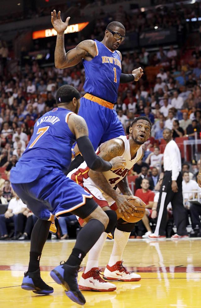 Miami Heat forward Udonis Haslem goes up for a shot against New York Knicks forward Carmelo Anthony (7) and forward Amar'e Stoudemire (1) during the first half of an NBA basketball game, Sunday, April 6, 2014, in Miami. (AP Photo/Wilfredo Lee)