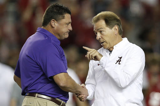 FILE - In this Nov. 4, 2017, file photo, LSU head coach Ed Orgeron, left, and Alabama head coach Nick Saban meet in the center of the field before an NCAA college football game, in Tuscaloosa, Ala. Eight SEC games have been postponed already with only Arkansas, Kentucky and South Carolina not affected _ yet. I do believe that Alabama and LSU ought to play this year, and I do believe were going to play somehow, some way, Orgeron said. (AP Photo/Brynn Anderson, File)