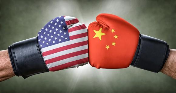 Two boxing gloves fist-bumping. One glove is emblazoned with the American flag and the other carries the Chinese colors.
