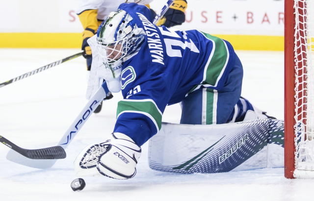 Vancouver Canucks goalie Jacob Markstrom, of Sweden, covers up the puck during the first period of an NHL hockey game against the Nashville Predators on Thursday, Dec. 6, 2018, in Vancouver, British Columbia. (Darry Dyck/The Canadian Press via AP)