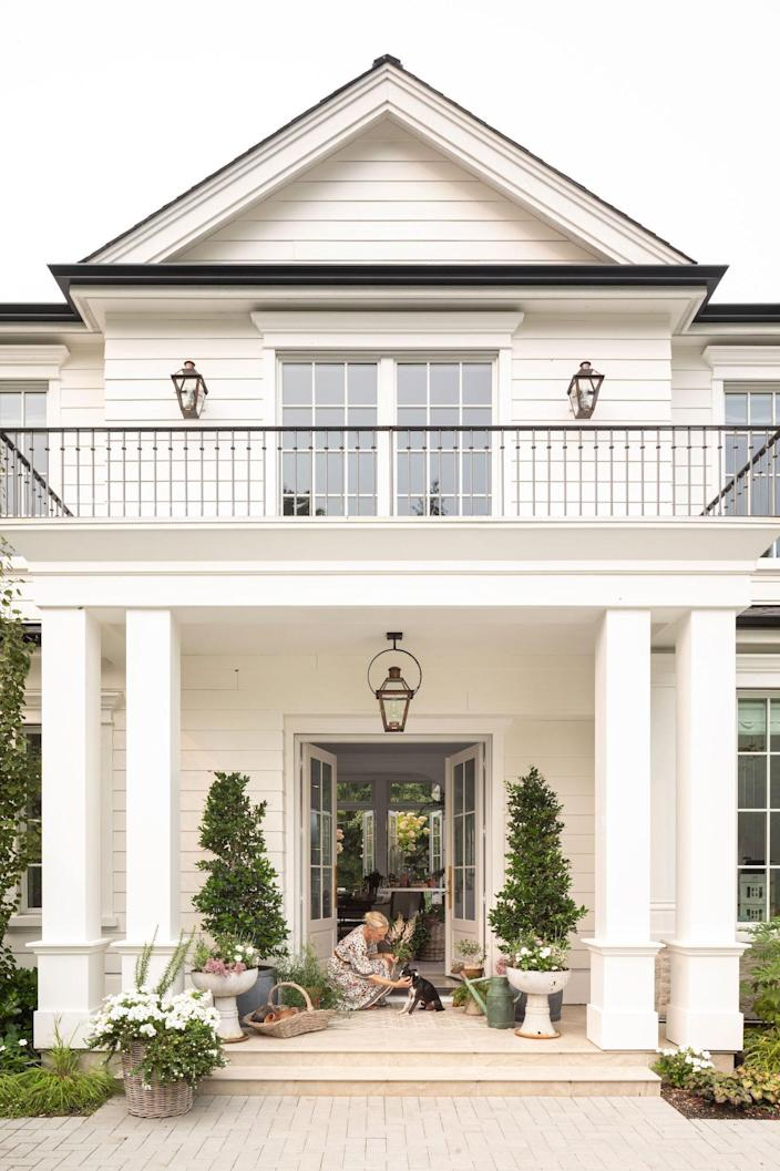 Kim Vaage Jones has a quiet moment with their family dog beneath a Colonial Revival–style lantern by Bevolo and planters by Stoops Designs.