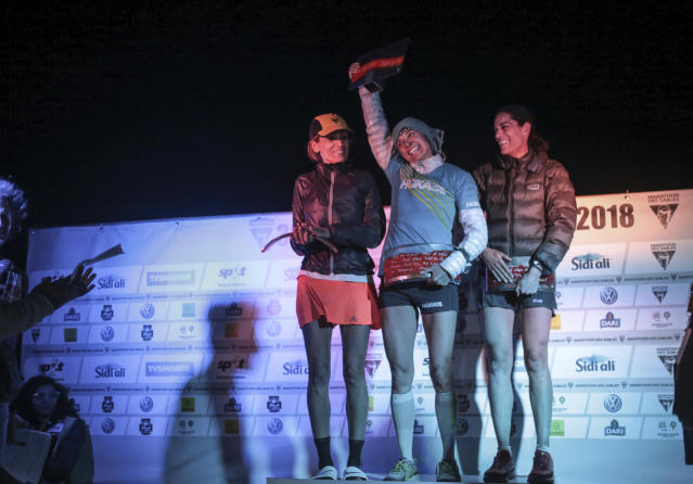 The female winners of the the 33rd edition of Marathon des Sables, Magdalena Boulet, center, Bouchra Eriksen, left, and Gemma Game, right, react as they receive their awards, in the Sahara desert, near Merzouga, southern Morocco, Friday, April 13, 2018. (AP Photo/Mosa'ab Elshamy)