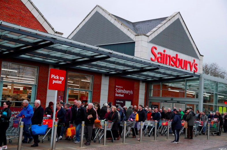 People queue to shop at Sainsbury's supermarket where the store had announced that the first hour of opening would be for elderly and vulnerable customers. (PA)
