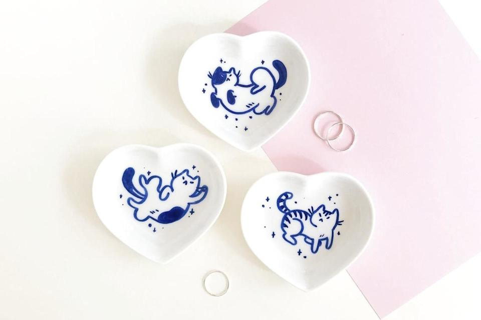 """Stash rings, keys and more little things in this <i>purr-fect</i>storage solution.<br /><br /><a href=""""https://www.awin1.com/cread.php?awinmid=6220&awinaffid=837483&clickref=HPThingsForKidsUsefulForAdultsToo-60a29811e4b090924806a856&ued=https%3A%2F%2Fwww.etsy.com%2Fshop%2FMadeByHakashi"""" target=""""_blank"""" rel=""""noopener noreferrer"""">MadeByHakashi</a> is a small business run by an illustrator who lives in the Netherlands. It has cute ceramics and trinket dishes that double up as home decor.<br /><br /><strong><a href=""""https://www.awin1.com/cread.php?awinmid=6220&awinaffid=837483&clickref=HPThingsForKidsUsefulForAdultsToo-60a29811e4b090924806a856&ued=https%3A%2F%2Fwww.etsy.com%2Flisting%2F856165929%2Fhand-painted-porcelain-trinket-dish"""" target=""""_blank"""" rel=""""noopener noreferrer"""">Get it fromMadeByHakashion Etsy for $15.21+ (available in four styles).</a></strong>"""