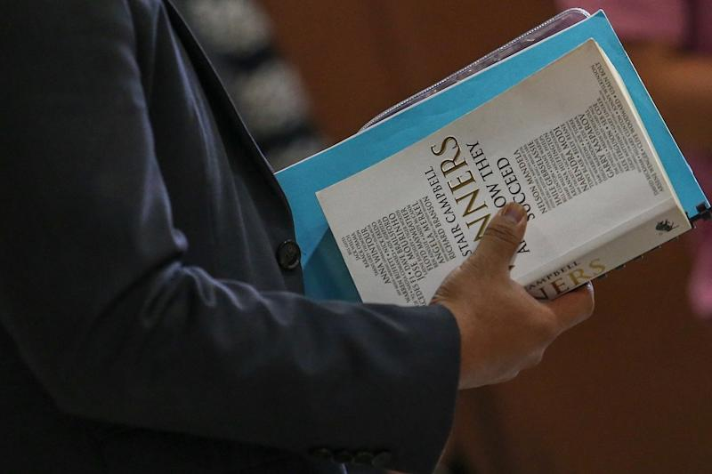 The book 'Winners and How They Succeed' by Alastair Campbell is seen being held by one of Datuk Seri Najib Razak's aides at the Kuala Lumpur Court Complex May 9, 2019 — Picture by Hari Anggara