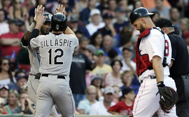 Chicago White Sox' Conor Gillaspie (12) is congratulated by teammate Alexei Ramirez after his two-run, home run off Boston Red Sox relief pitcher Koji Uehara during the ninth inning of a baseball game at Fenway Park in Boston, Thursday, July 10, 2014. At right is Boston Red Sox catcher David Ross. (AP Photo/Charles Krupa)