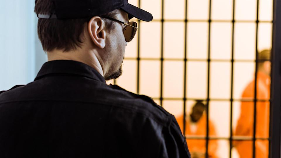 rear view of prison officer standing near prison cell with criminals.