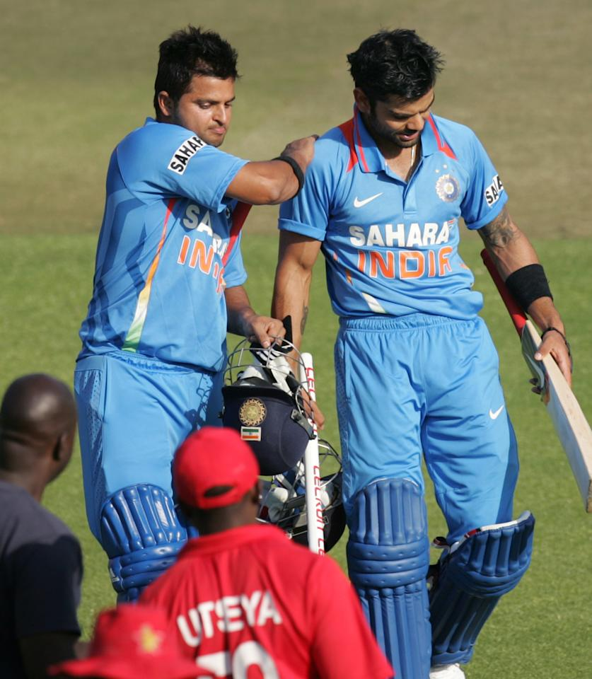 India's captain Virat Kohli (R) receives a pat on the back from teammate Suresh Raina after their victory during the 3rd match of the 5 cricket ODI series between Zimbabwe and India at Harare Sports Club on July 28, 2013. AFP PHOTO / JEKESAI NJIKIZANA