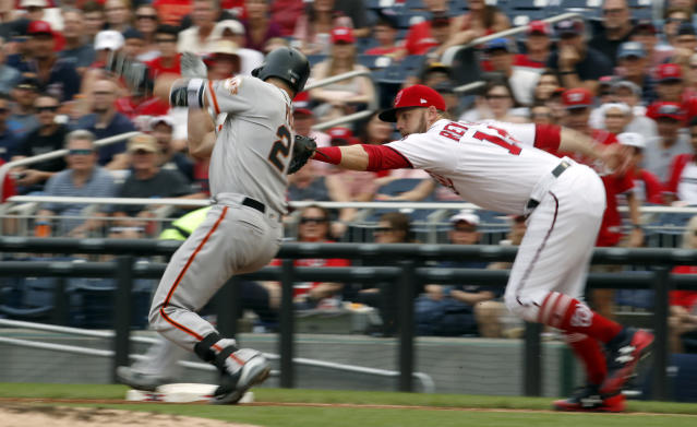 San Francisco Giants' Buster Posey (28) is tagged out by Washington Nationals first baseman Mark Reynolds (14) before he reaches base during the third inning of a baseball game at Nationals Park, Sunday, June 10, 2018, in Washington. (AP Photo/Alex Brandon)