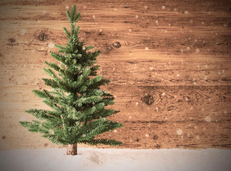 Retro Christmas Tree On Brown Wooden Background With Snow. Copy Space For Advertisement. (Photo: Nelosa via Getty Images)