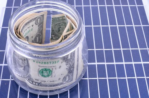 A jar of money on top of a solar panel