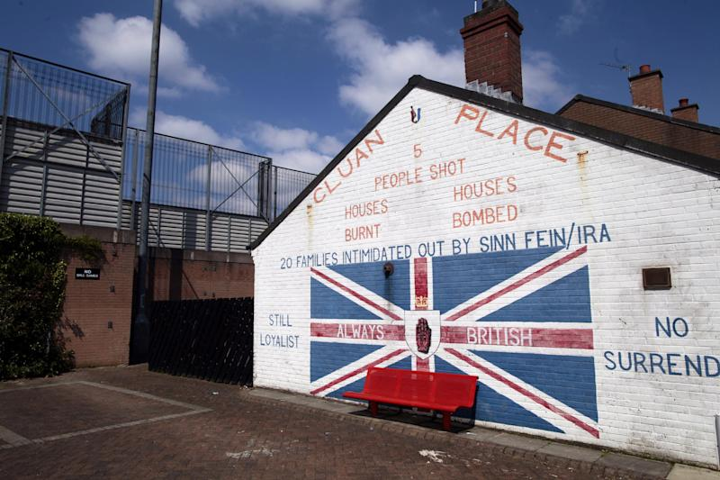 In this photo taken on June 10, 2013, a loyalist mural adorns a wall beside a peace wall that divides the Protestant Cluan Place from the Catholic Short Strand area, in the Protestant Cluan Place area of East Belfast, Northern Ireland. When President Obama comes to Belfast, he's expected to praise a country at peace and call for walls that separate Irish Catholics and British Protestants to come tumbling down. Barely a 10-minute walk from where the U.S. leader is speaking Monday, June 17, 2013, those walls have kept growing in size and number throughout two decades of slow-blooming peace. Residents on both sides of the battlements today insist they must stay to keep violence at bay. (AP Photo/Peter Morrison)