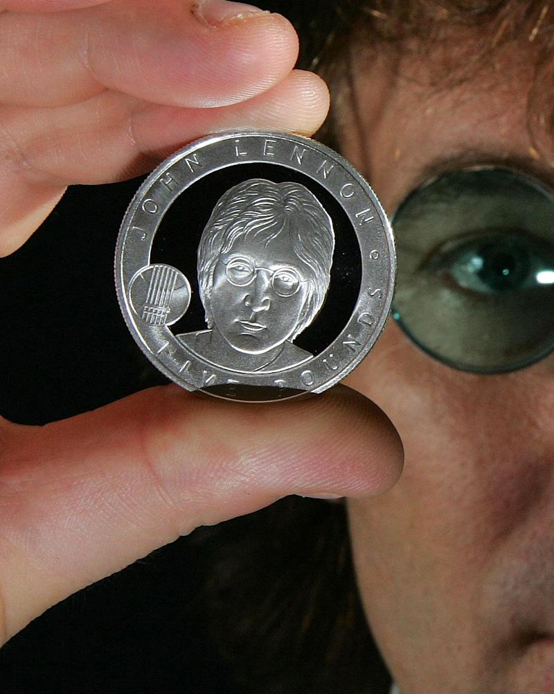 In this image dated Oct. 18, 2010, released by the British Royal Mint, showing John Lennon look-a-like Alan Swoffer, poses with the new John Lennon £5 coin which goes on sale Friday Oct. 29, 2010.  The new coin depicting rock icon John Lennon who is being honored with an official British commemorative coin.  The former member of the Beatles singer songwriter Lennon was chosen by a public vote to be honoured with the coin with a face value of 5 pounds (US $ 8) but will be sold at 45 pounds (US $ 71.68) in a limited edition on sale Friday. The former Beatle will join William Shakespeare, Winston Churchill, Charles Darwin, Florence Nightingale among British luminaries whose images have graced special coins. (AP Photo/ Geoff Caddick, The Royal Mint) ** Editorial Use Only **