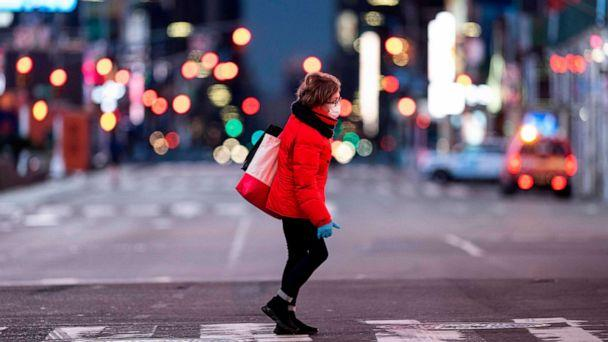 PHOTO: A woman walks through an almost-deserted Times Square in the early morning hours, on April 23, 2020, in New York City. (Johannes Eisele/AFP via Getty Images)