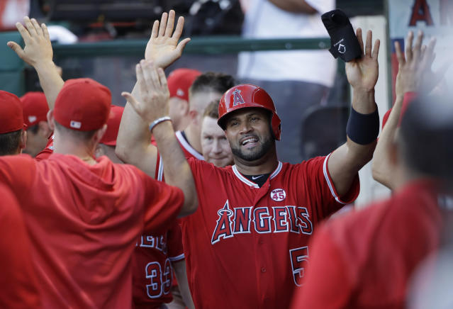 Los Angeles Angels' Albert Pujols, center, is greeted in the dugout after scoring on a double by David Fletcher during the fourth inning of the tema's baseball game against the Pittsburgh Pirates on Wednesday, Aug. 14, 2019, in Anaheim, Calif. (AP Photo/Marcio Jose Sanchez)