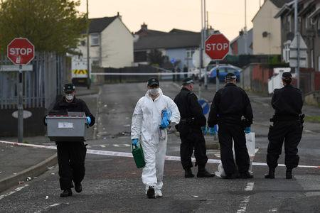 FILE PHOTO: Police officers carry a box of evidence as they leave the scene where the 29-year-old journalist Lyra McKee was shot dead, in Londonderry, Northern Ireland April 19, 2019. REUTERS/Clodagh Kilcoyne/File Photo