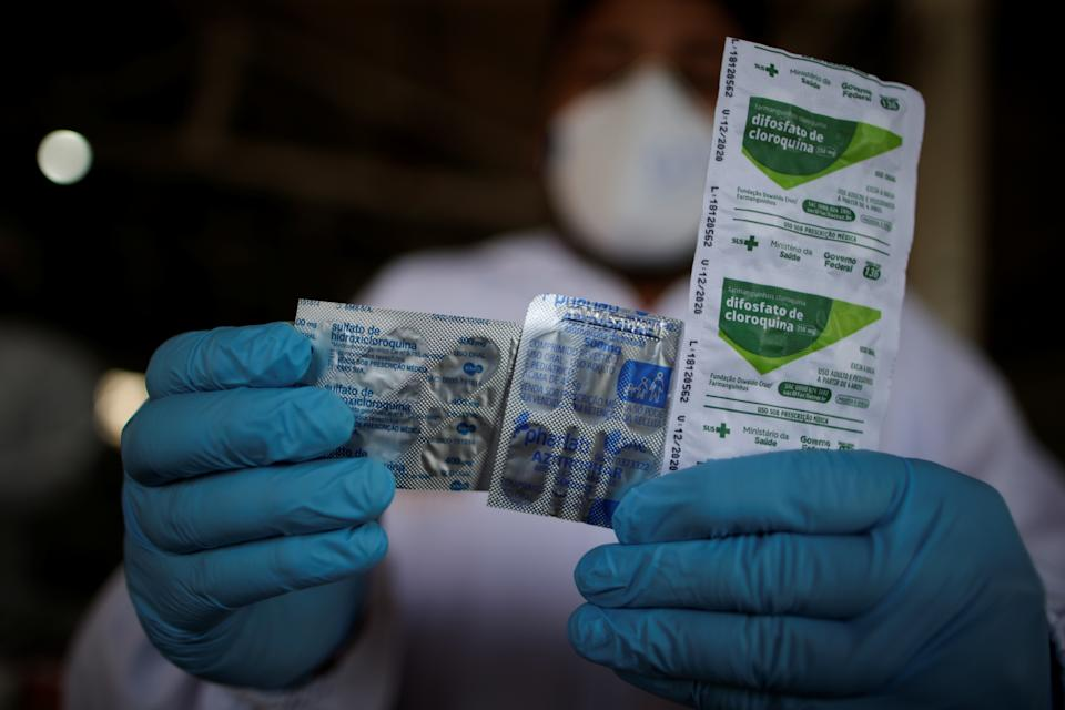 A healthcare worker holds a packet of hydroxychloroquine sulfate, azitrophar and chloroquine diphosphate, which some doctors have been distributing to people who have tested positive for COVID-19, as part of a remedy kit for treatment, at the riverside community Santo Ezequiel Moreno, as healthcare workers travel to riverside communities during the coronavirus disease (COVID-19) outbreak, in the municipality of Portel, at Marajo island, Para state, Brazil, June 5, 2020. REUTERS/Ueslei Marcelino     SEARCH