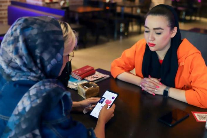 """Iranian woman Atefeh Khani and her friend checks the """"Hamdam"""" dating app on her phone in a cafe in Tehran"""