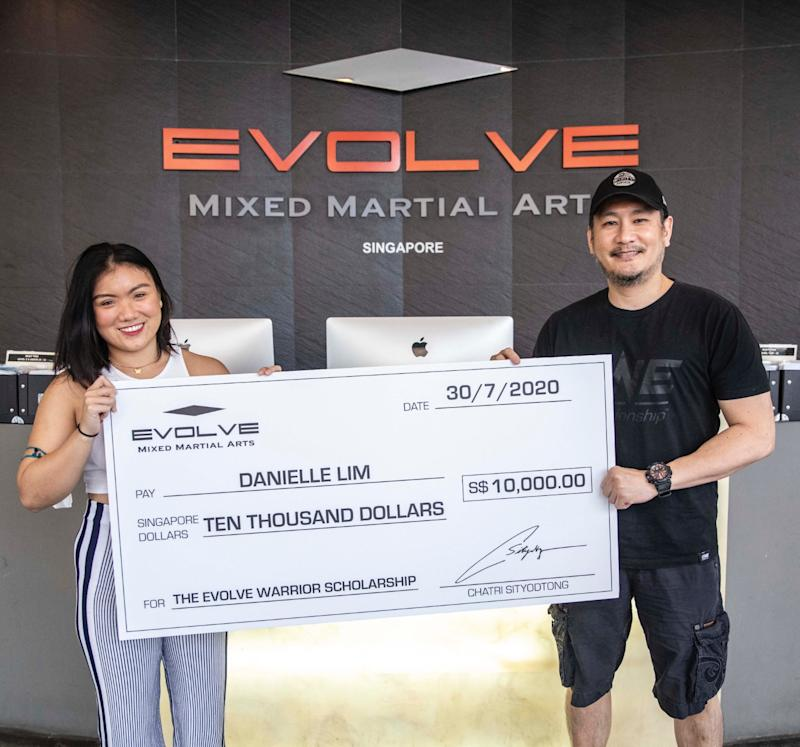 Singapore wrestler Danielle Lim (left) receives the Evolve Warrior Scholarship from Evolve MMA chairman Chatri Sityodtong. (PHOTO: Evolve MMA)