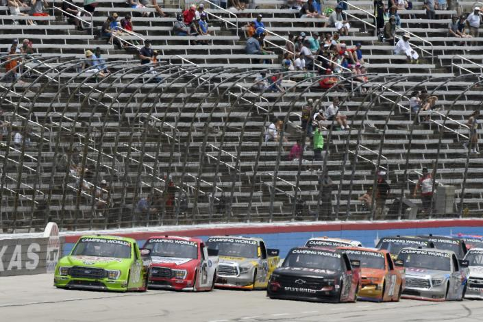 Todd Gilliland, left front, and Chase Elliott, right front, lead the field into the front stretch coming out of Turn 4 during a NASCAR Truck Series auto race at Texas Motor Speedway in Fort Worth, Texas, Saturday, June 12, 2021. (AP Photo/Larry Papke)