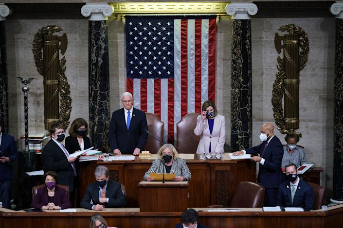<p>Vice President Mike Pence and Speaker of the House Nancy Pelosi, D-Calif., prepare to read the final certification of Electoral College votes cast in November's presidential election during a joint session of Congress after working through the night, at the Capitol on 7 January 2021 in Washington, DC.</p> (Getty Images)