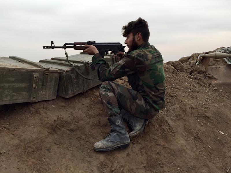 A pro-regime gunman holds a position at a military airport held by Syrian troops and pro-regime militias in the northeastern Syrian city of Deir Ezzor on December 12, 2014