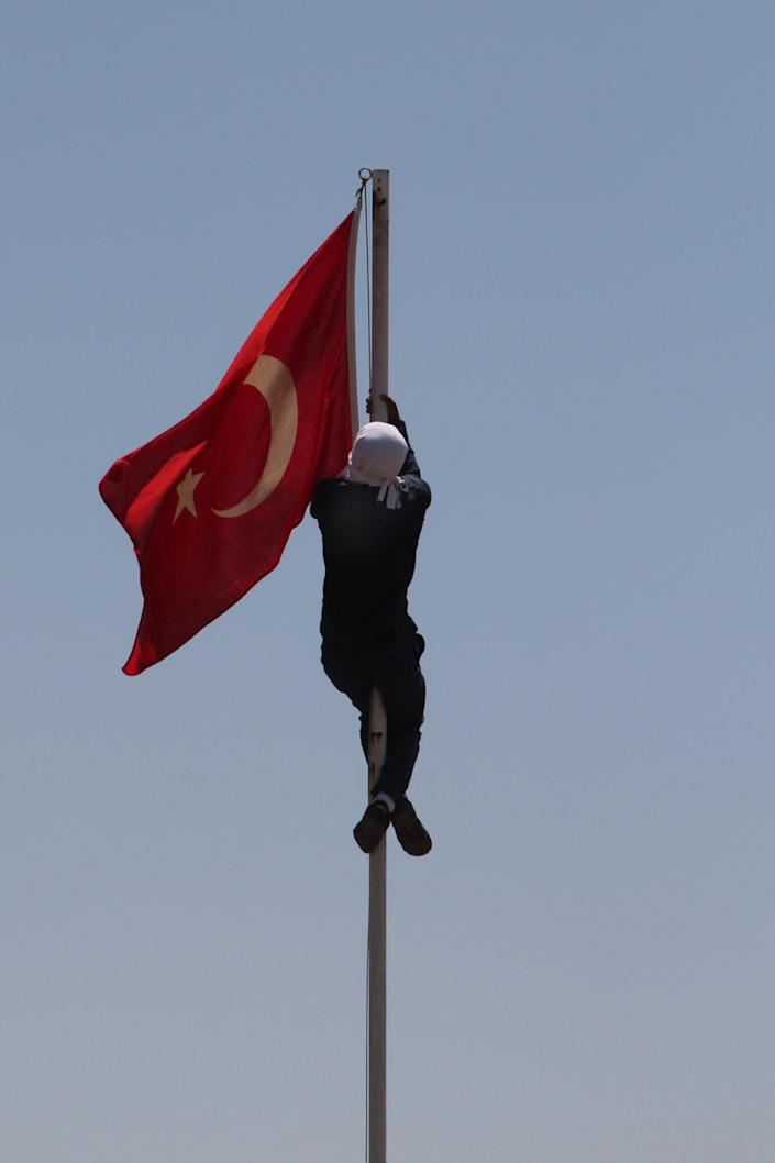 A masked Kurdish protestor try to pull down a Turkish flag on June 8, 2014 in Diyarbakir, eastern Turkey, after a man was killed during clashes with soldiers the night before in Lice (AFP Photo/Ilyas Akengin )
