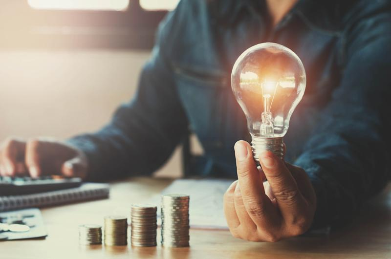A man sitting at a table holding a light bulb in one hand, with the other hand on a calculator and an ascending stack of coins laying in front of him on the table.