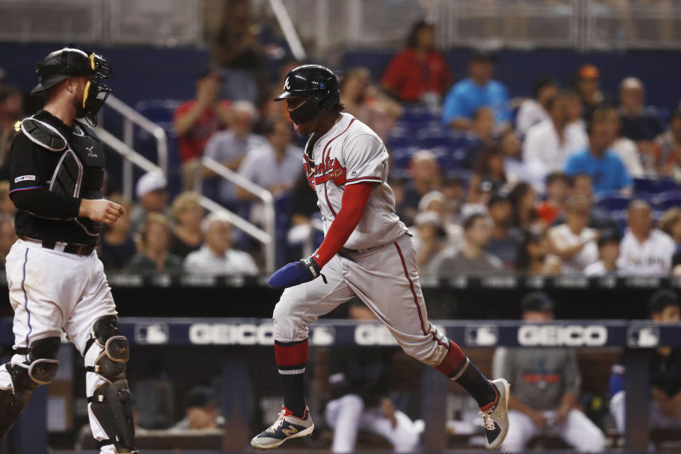 Atlanta Braves' Ronald Acuna Jr., right, celebrates as he scores during the eighth inning of a baseball game against the Miami Marlins, Saturday, Aug. 10, 2019, in Miami. (AP Photo/Brynn Anderson)