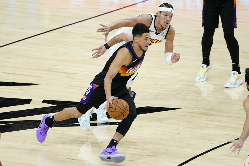 Phoenix Suns guard Devin Booker, front, drives as Denver Nuggets forward Aaron Gordon defends during the second half of Game 1 of an NBA basketball second-round playoff series, Monday, June 7, 2021, in Phoenix. (AP Photo/Matt York)