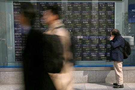 A man looks at an electronic stock quotation board outside a brokerage in Tokyo, Japan February 9, 2018.  REUTERS/Toru Hanai
