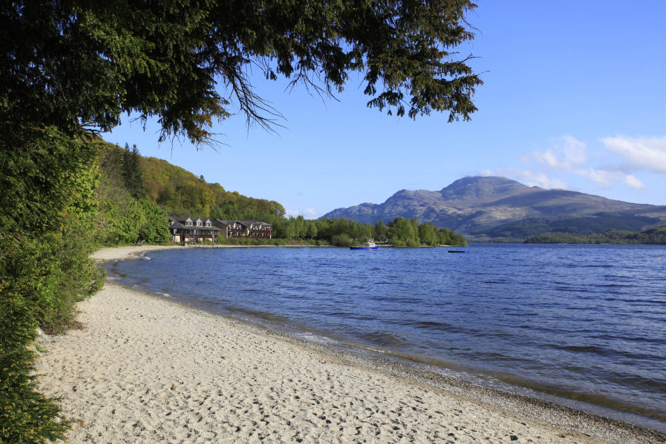 The sandy beach at luss which is located on the west side of loch lomond.  The loch Lomond hotel and lodges is visible beyond. [Photo: Visit Scotland]