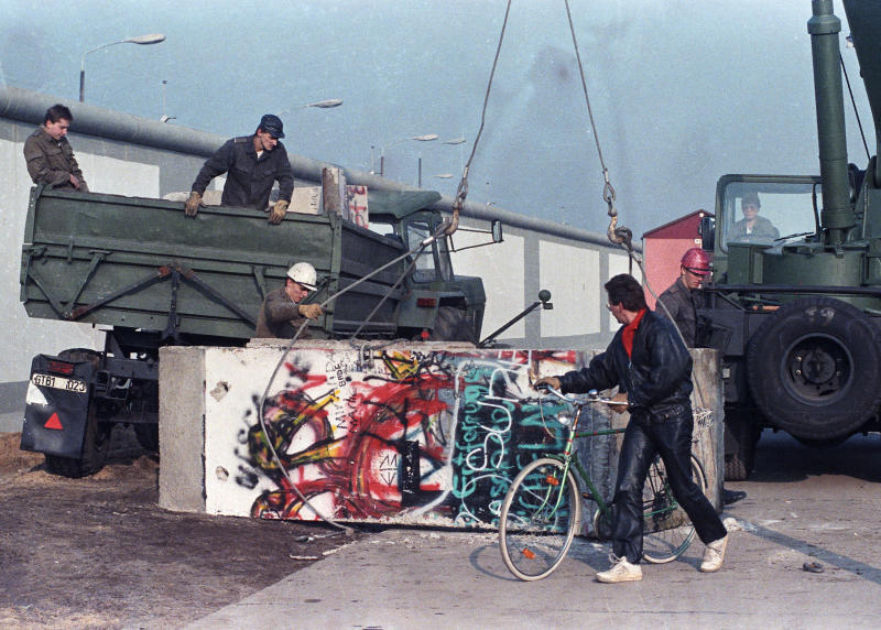 East German workers remove concrete parts of the Berlin Wall and load them onto trucks at the recently opened border crossing point at Potsdam Platz on Nov. 14, 1989. (Photo: Wolfgang Rattay/Reuters)