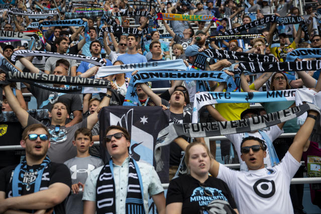 In this July 13, 2019, photo, Minnesota United fans chant and hold cup scarves in anticipation of the start of the MLS team's soccer match against FC Dallas in St. Paul, Minn. The first season for Minnesota United at Allianz Field has been a sold-out success. As the Loons prepare for their first MLS playoff game, they'll have their raucous supporters section behind them to help. (Alex Kormann./Star Tribune via AP)