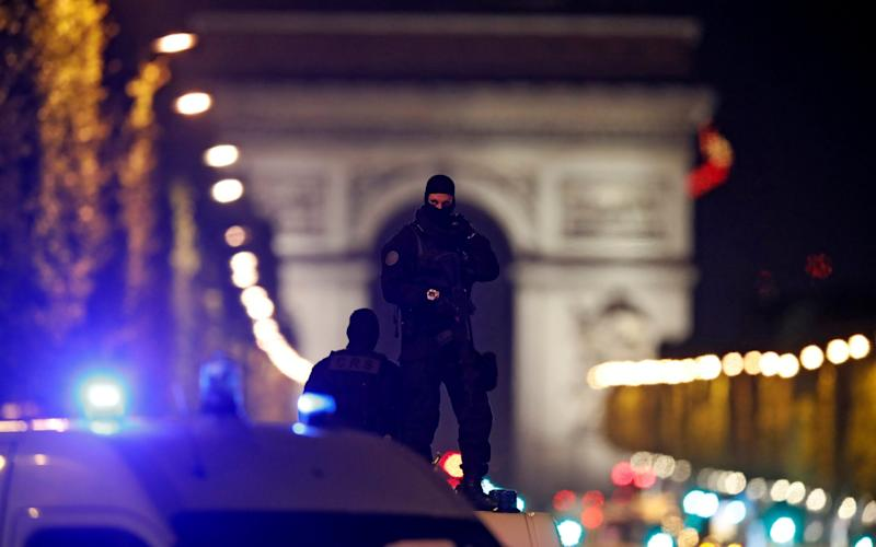 Masked police stand on top of their vehicle on the Champs Elysees after the shooting - REUTERS