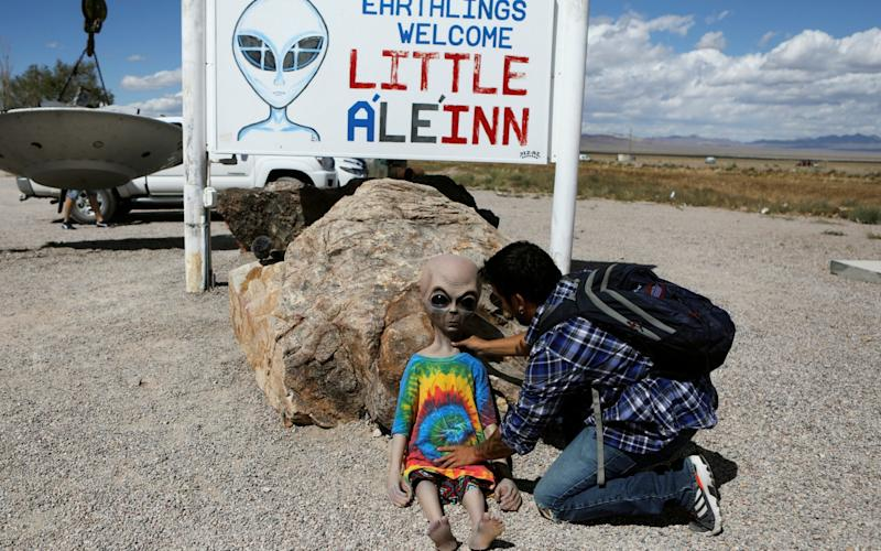 An attendee poses an alien doll at the Little A'Le'Inn as an influx of tourists responding to a call to 'storm' Area 51, a secretive U.S. military base believed by UFO enthusiasts to hold government secrets about extra-terrestrials, is expected - REUTERS