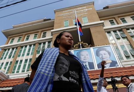 "A supporter of Cambodia's late an anti-government figure and the head of a grassroots advocacy group, ""Khmer for Khmer"" Kem Ley stands outside the court building in Phnom Penh"