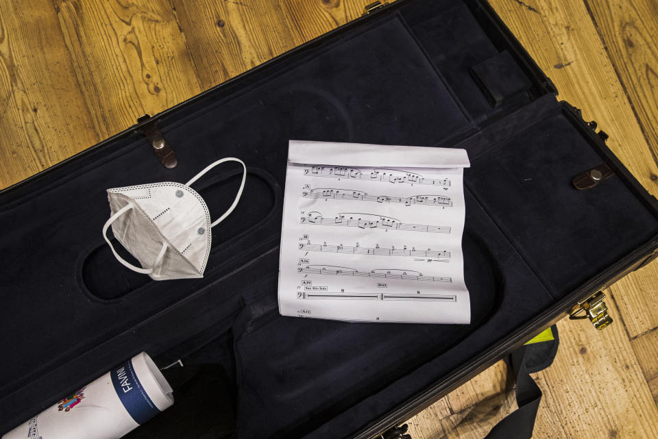 A sanitary mask lies in a saxophone container during the Giuseppe Verdi jazz orchestra rehearsals at the Giuseppe Verdi Music Conservatory, in Milan, Italy, Friday, May 7, 2021. Whatever the instrument, flute, violin or drums, students at Italy's oldest and largest music conservatory have been playing behind plexiglass screens during much of the pandemic as the Conservatory found ways to preserve instruction throughout Italy's many rolling lockdowns. (AP Photo/Antonio Calanni)