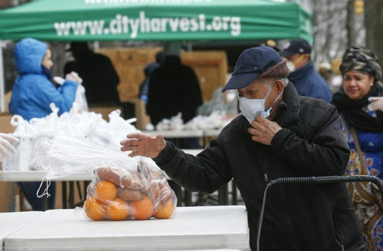 A man receives bags with food from City Harvest food bank (AFP Photo/Kena Betancur)