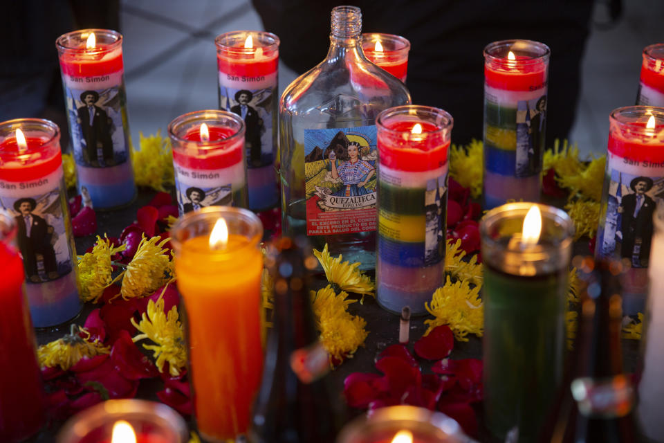 A bottle of liquor is surrounded by burning candles with images of folk saint Maximon, an Indigenous character worshipped mainly by Indigenous people, inside a temple known as Maximon church on his feast day in San Andres Itzapa, Guatemala, Wednesday, Oct. 28, 2020. To help curb the spread of the new coronavirus, the annual celebration was limited to local residents who waited in line to enter the church little by little, and it was closed to pilgrims who normally travel here from across the country. (AP Photo/Moises Castillo)