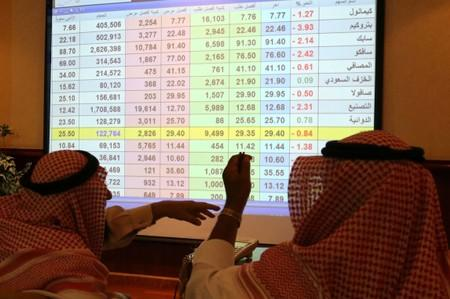 Saudi men look to a screen showing stock prices at ANB Bank, in Riyadh