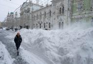 A woman walks past a heap of snow in central Moscow