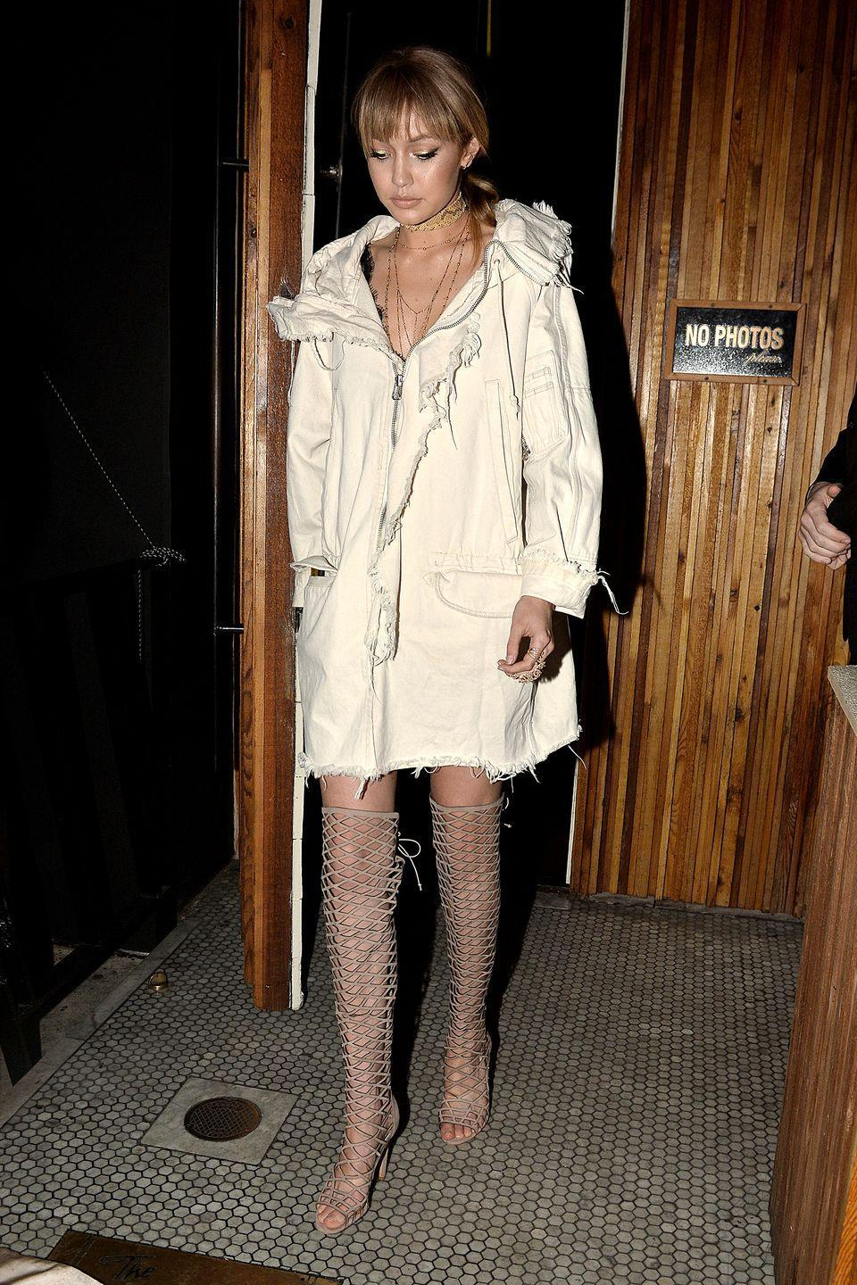 <p>Hadid steps out in her signature off-white color, wearing an anorak coat as a dress, paired with thigh-high lace ups.</p>