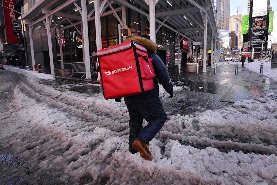 A DoorDash food delivery person makes his way through slushy snow in Times Square in New York, US. Photo: Anthony Behar/Sipa USA