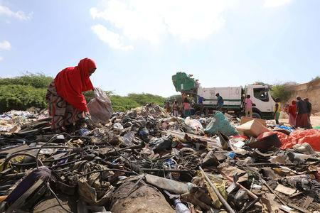A woman searches for plastic litter at a garbage dump to be recycled into roofing tiles at the Envirogreen recycling plant in Mogadishu, Somalia January 13, 2019. Picture taken January 13, 2019. REUTERS/Feisal Omar