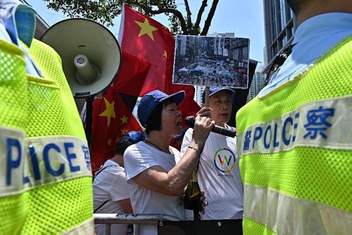 A small group of Beijing loyalists welcomed the jail sentences (AFP Photo/Anthony WALLACE)