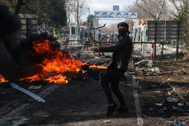 A migrant reacts as Greek riot police guard the border gate in Kastanies village on Saturday, Feb. 29, 2020. (AP)